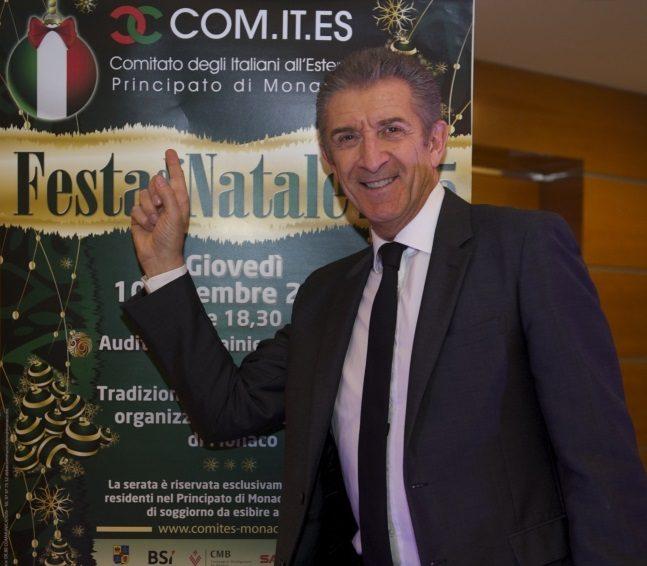 Ezio davanti al cartellone della Festa di Natale del Comites 2015
